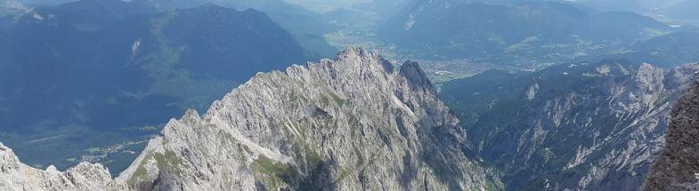 Graue Berggipfel vor Tal