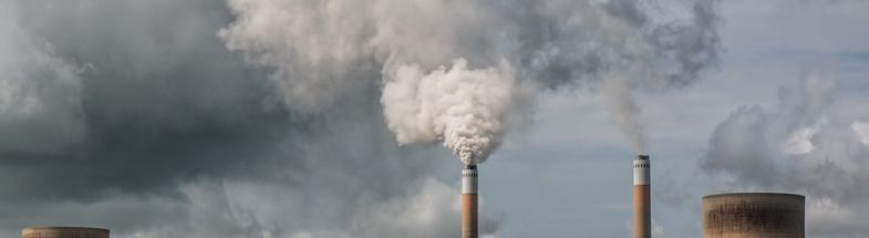 Schornsteine und Kühltürme vor Rauchwolken