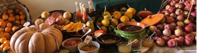 Buffet mit Äpfeln, Mandarinen, Granatäpfeln und unterschiedlichen Fruchtaufstrichen.
