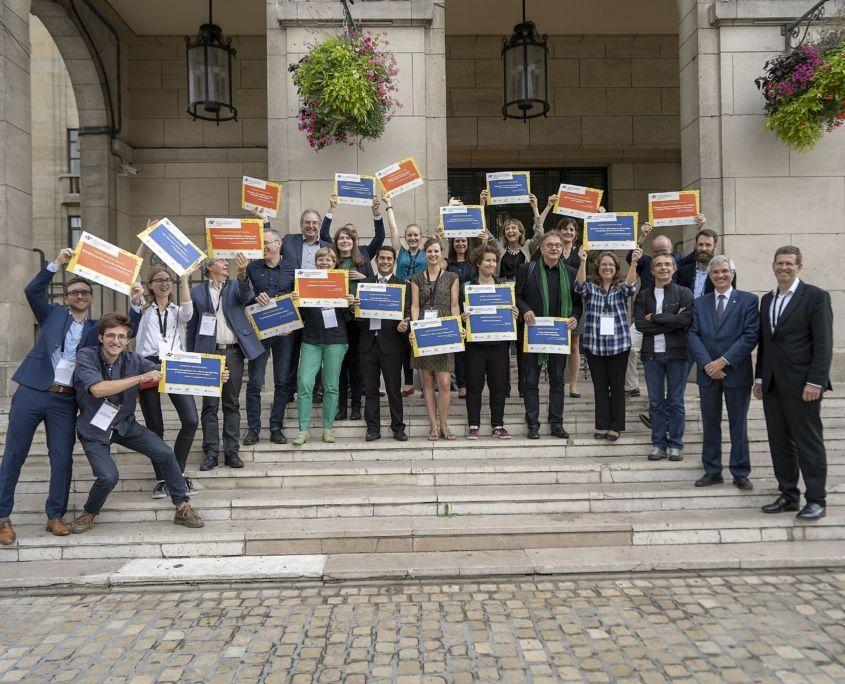Gewinner des Ideenwettbewerbs mit Urkunden auf Treppe