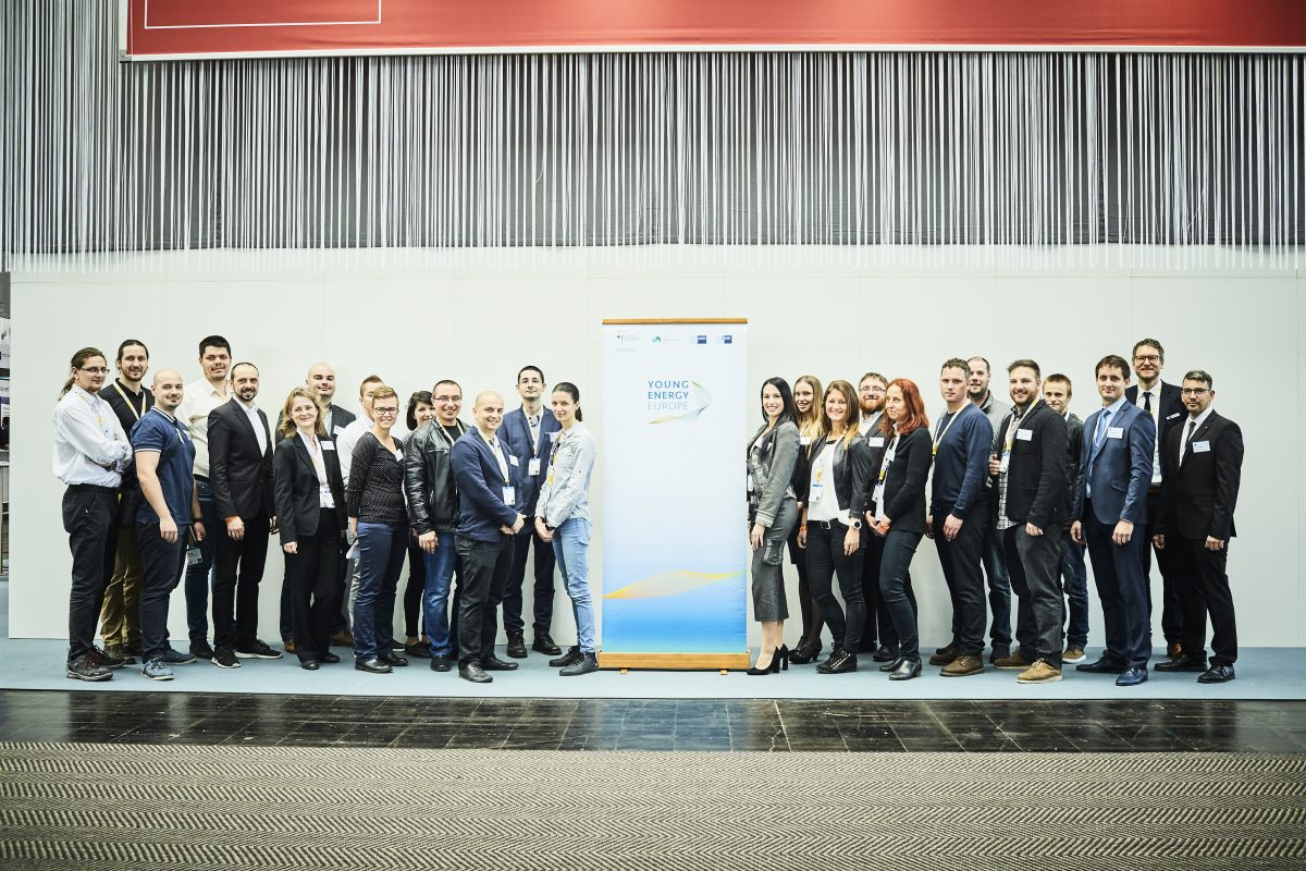 Group photo of about 30 people on a stage. In the middle is a roll-up of Young Energy Europe.