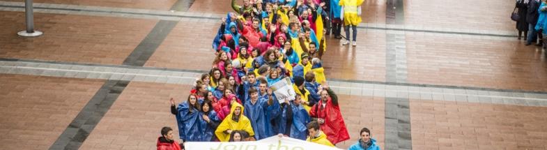 Personengruppe in Form einer Windmühle vor dem EU-Parlament.