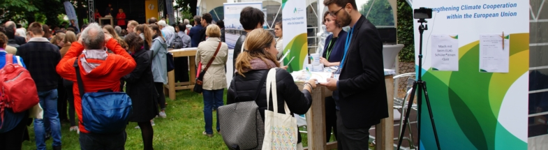 There is a booth with people. In the foreground a young man talks to a woman about a booklet.