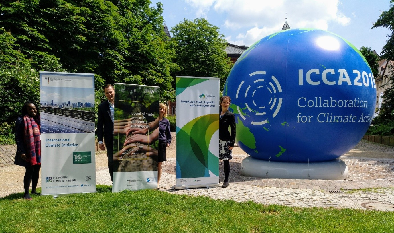 There are three exhibition walls and next to them are people. On the right of the photo a large blue ball can be seen representing the earth with the ICCA 2019 inscription.