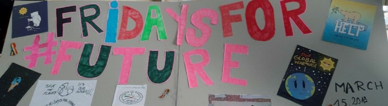 "Big banner, on which there is written ""Fridays for #Future"" next to some posters. In he background there is a class room."