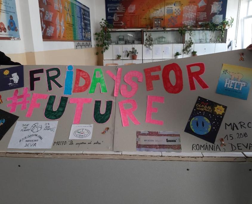 """Großer Banner, auf dem """"Fridays for #Future"""" steht und einige Plakate abgebildet sind. Im Hintergrund ein Klassenzimmer."""