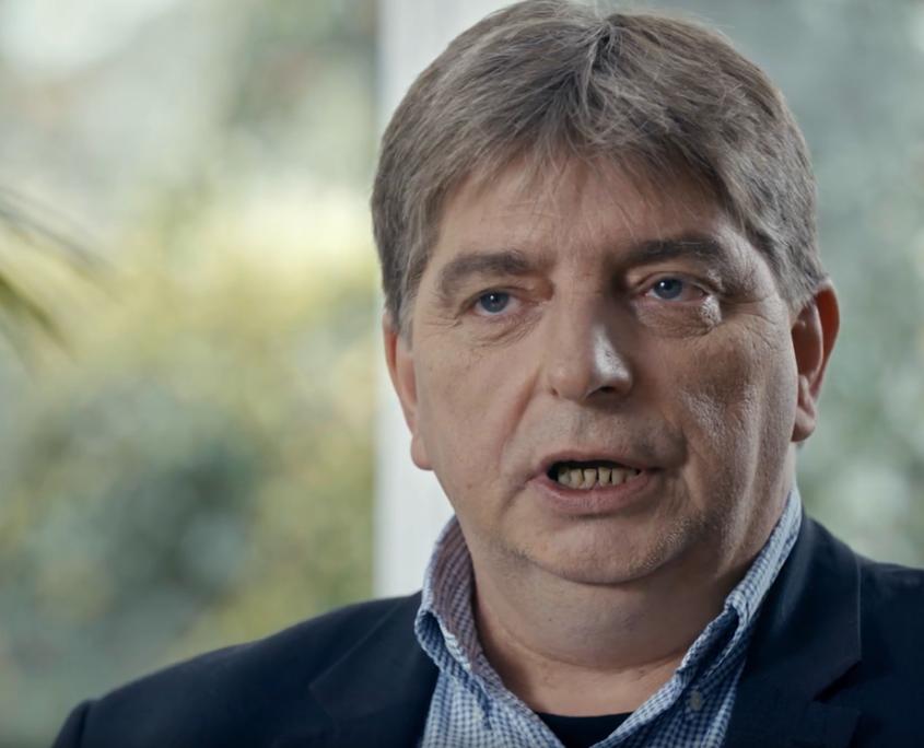 Mann mit grauen Haaren spricht in Kamera. Im Hintergrund sind einzelne Zimmerpflanzen zu sehen.