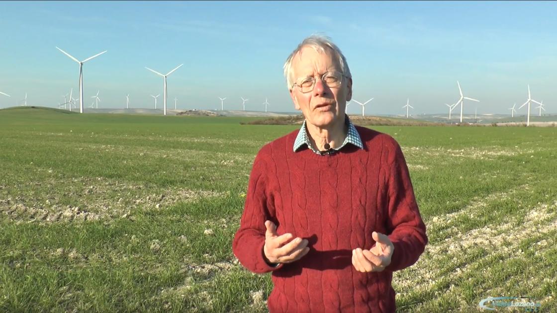 Mann mit rotem Pullover steht vor hügeliger andalusischer Landschaft mit Windrädern