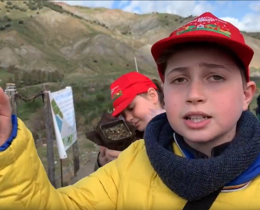 Boy with yellow jacket and red cap standing in front of Etna landscape. In the background other children.