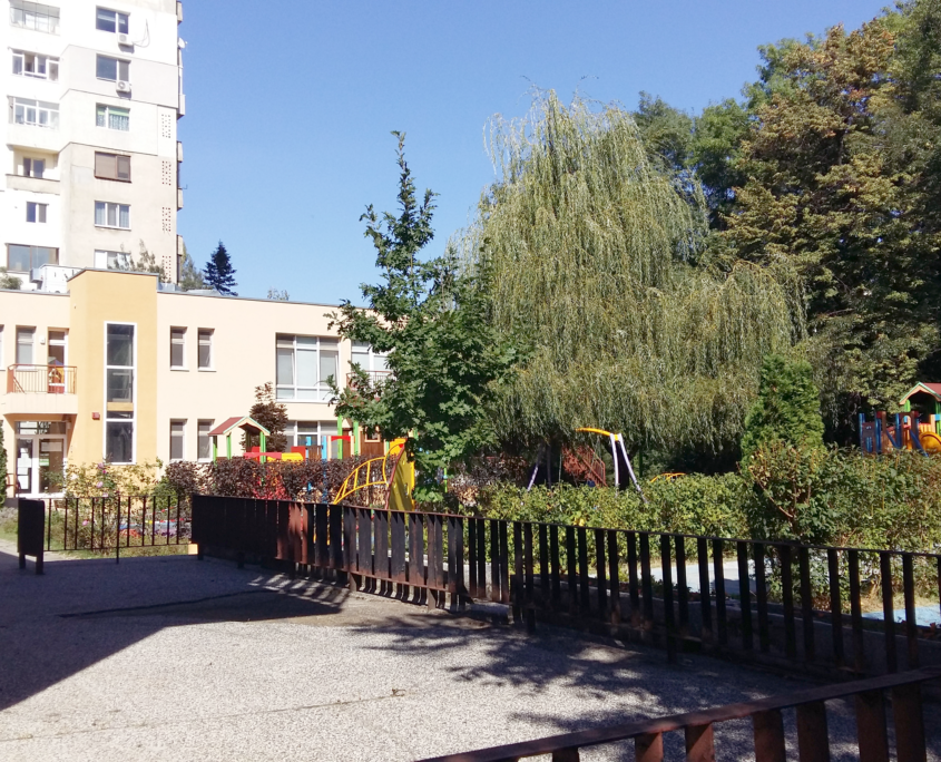 In the foreground a playground. Behind it a yellow painted kindergarten between trees. In the background a prefabricated building.