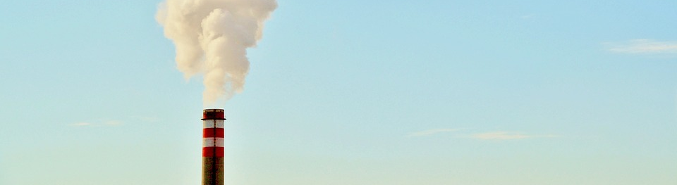 Upper part of an industrial chimney which leaves white smoke to the blue sky
