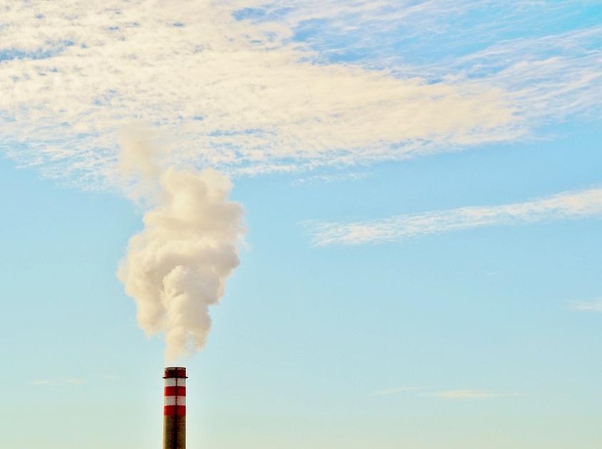 Oberer Teil eines Schornsteins, der weißen Rauch in den blauen Himmel ausstößt