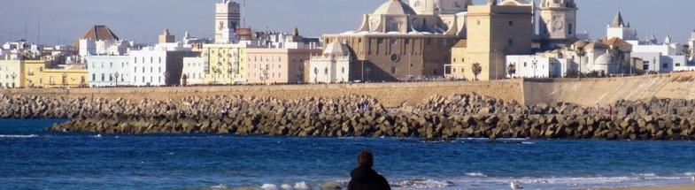 Mann läuft am Strand von Cadiz. Im Hintergrund die Kathedrale.