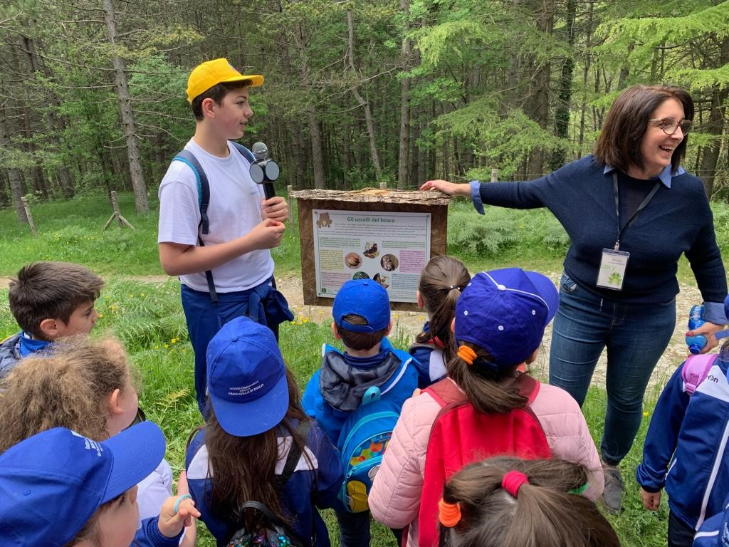 Children are standing in front of the forest. A boy explains an information sign to the toad path bufo bufo