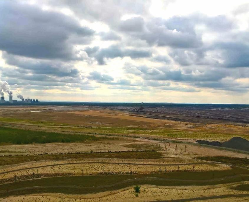 Blick über einen Tagebau. Im Hintergrund rauchende Türme