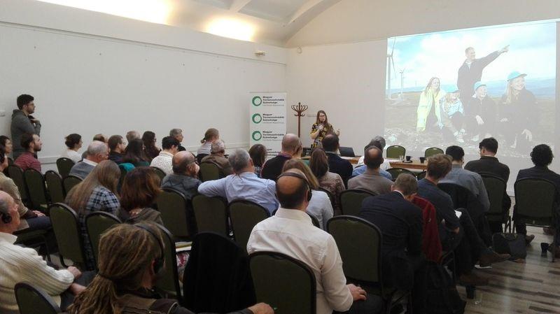 Eine Frau hält eine Präsentation vor einem Publikum. Das Publikum besteht aus ca. 50 Personen.